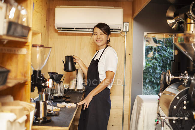 Japanese woman wearing apron standing in an Eco Cafe, preparing coffee, smiling in camera. — Stock Photo