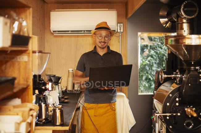 Japanese man wearing hat and glasses standing in an Eco Cafe, holding laptop computer, smiling in camera. — Stock Photo