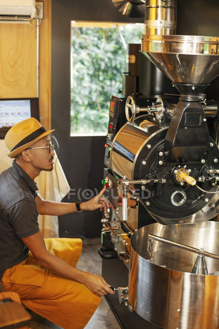 Japanese man wearing hat and glasses sitting in an Eco Cafe, operating coffee roaster machine. — Stock Photo