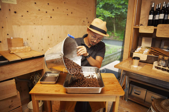Japanese man wearing hat and glasses sitting in an Eco Cafe, pouring freshly roasted coffee beans into metal tray. — Stock Photo