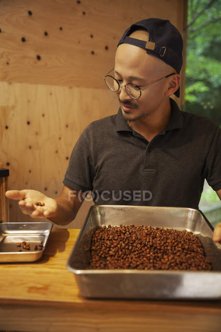 Japanese man wearing baseball cap and glasses standing in an Eco Cafe, checking freshly roasted coffee beans. — Stock Photo
