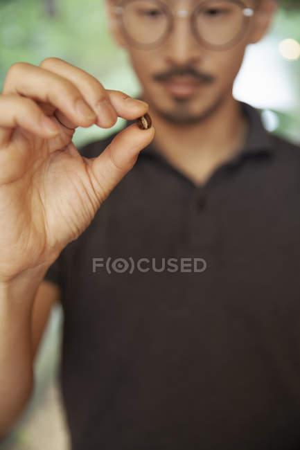 Gros plan de l'homme tenant un grain de café torréfié . — Photo de stock