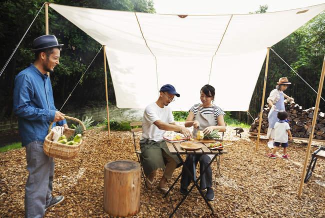Grupo de homens e mulheres japoneses e criança reunidos em volta de uma mesa abaixo de um dossel, preparando verduras . — Fotografia de Stock