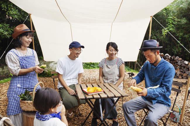 Grupo de homens e mulheres japoneses com a criança reuniu-se em volta de uma mesa abaixo de um dossel, preparando verduras . — Fotografia de Stock