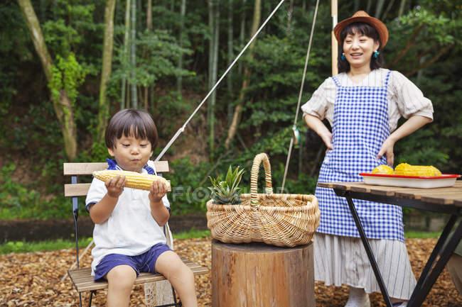 Femme japonaise debout à l'extérieur, portant chapeau et tablier et garçon assis sur une chaise, mangeant du maïs sur l'épi . — Photo de stock