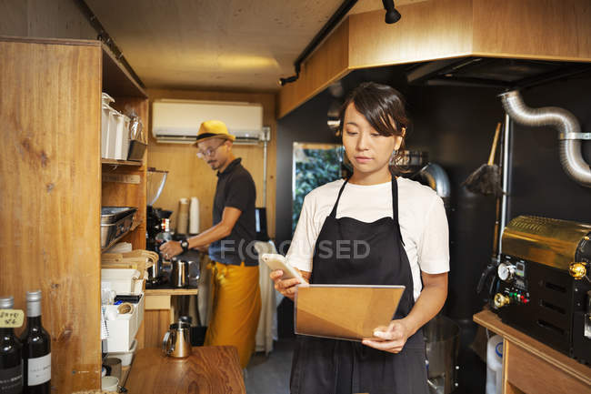 Japanese woman and man working in an Eco Cafe, preparing coffee, using mobile phone. — Stock Photo