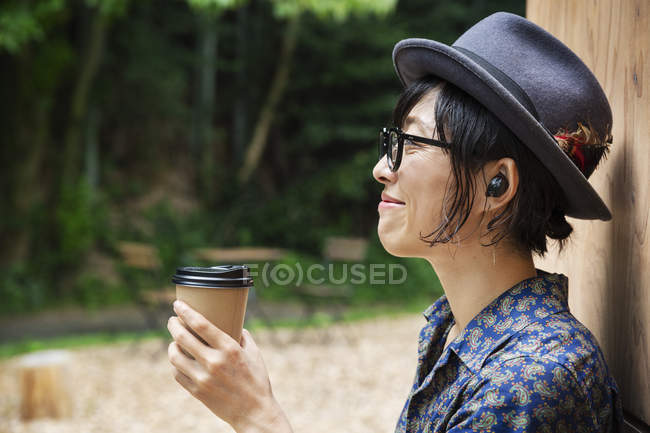 Japanese woman in glasses and hat standing outside Eco Cafe, holding paper cup. — Stock Photo