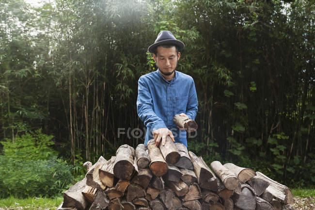 Japonais portant un chapeau debout à l'extérieur, empilant des bûches de bois de chauffage . — Photo de stock