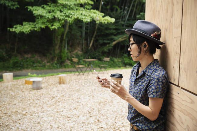 Японка в очках и шляпе стоит у Эко-кафе, держа в руках бумажный стаканчик. — стоковое фото
