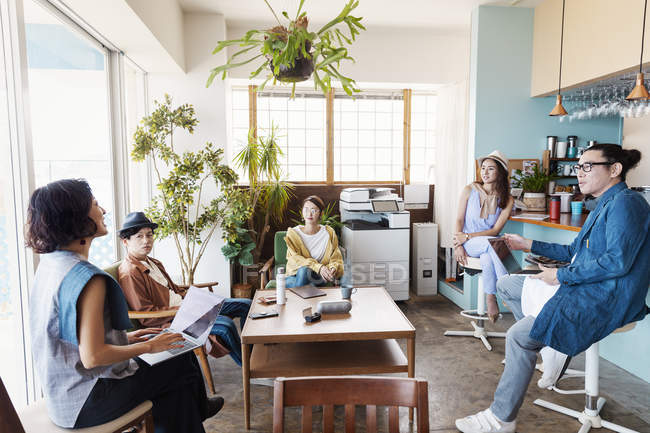 Group of Japanese businesspeople working on laptop computers in a co-working space. — Stock Photo