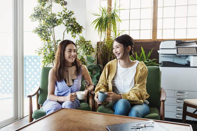 Two female Japanese professionals sitting in chairs and talking with cups of drinks in a co-working space, smiling at each other. — Stock Photo