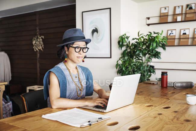 Femme japonaise professionnelle assise à une table dans un espace de co-travail, à l'aide d'un ordinateur portable . — Photo de stock