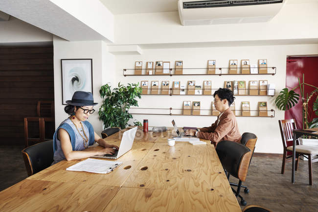Male and female Japanese professionals working on laptop computers in a co-working space. — Stock Photo