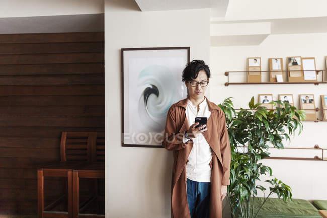 Profissional japonês masculino em pé em um espaço de co-trabalho, olhando para o smartphone . — Fotografia de Stock