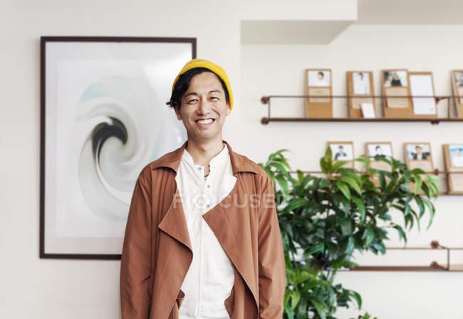 Männlicher japanischer Profi steht in einem Co-Working Space und lächelt in die Kamera. — Stockfoto