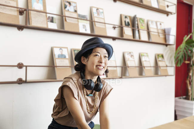 Female Japanese professional wearing hat and headphones, sitting in a co-working space. — Stock Photo
