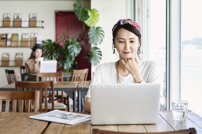 Japanerin arbeitet am Laptop im Co-Working Space, Kollegin im Hintergrund. — Stockfoto