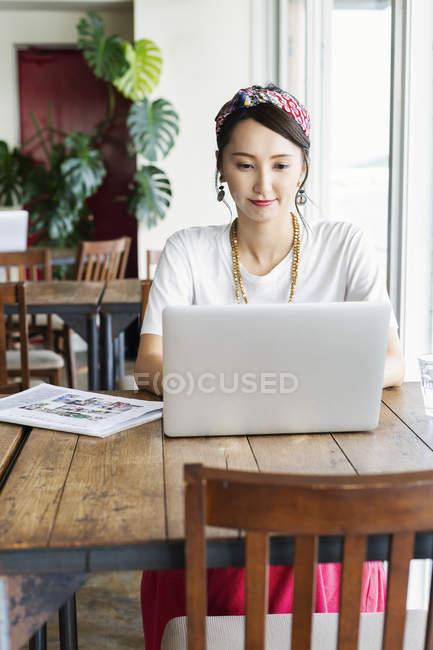 Японка работает над ноутбуком в коворкинге. — стоковое фото