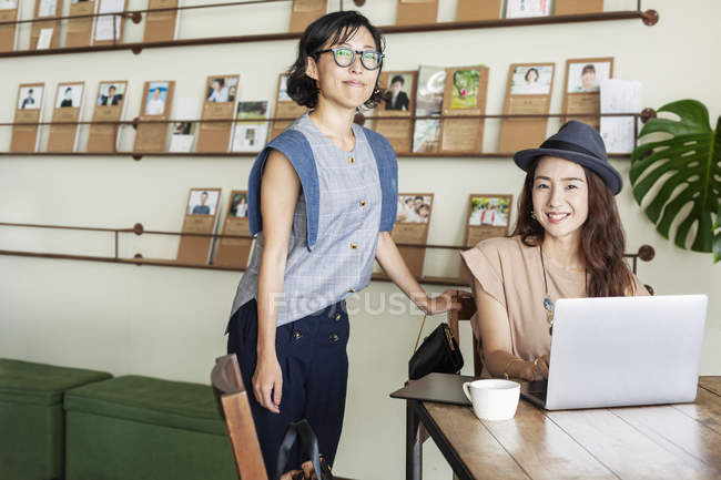 Two female Japanese professionals at a table in a co-working space, using laptop computer. — Stock Photo