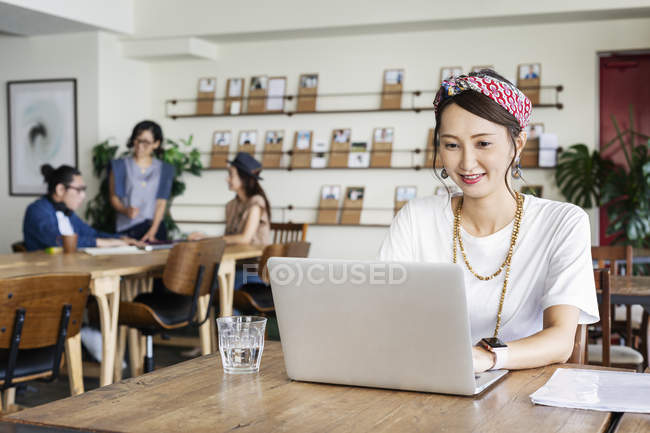 Japanese woman working on laptop in a co-working space, colleagues in background. — Stock Photo