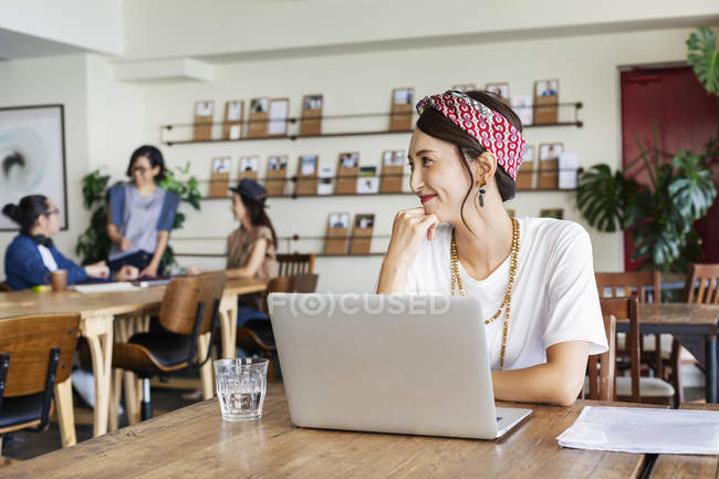 Donna giapponese che lavora su laptop in uno spazio di co-working, colleghi in background . — Foto stock