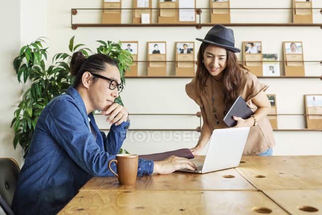 Professionnels japonais hommes et femmes à une table dans un espace de co-travail, à l'aide d'un ordinateur portable . — Photo de stock