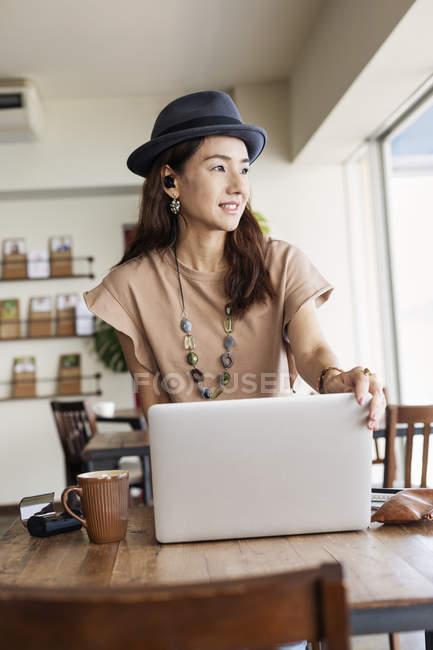 Японская женщина-специалист, сидящая за столом в коворкинге, используя ноутбук. — стоковое фото