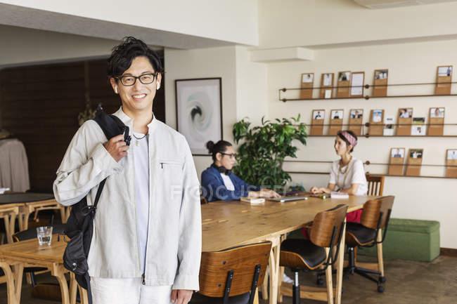 Мужчина стоит перед японскими специалистами, работающими над ноутбуком в коворкинге. — стоковое фото