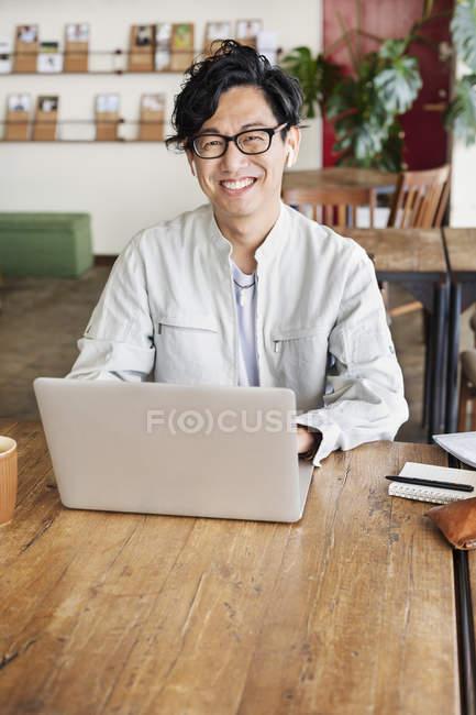 Homme japonais professionnel assis à une table dans un espace de co-travail, à l'aide d'un ordinateur portable . — Photo de stock