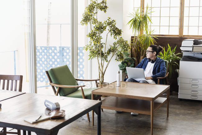 Male Japanese professional sitting at a table in a co-working space, using laptop computer. — Stock Photo