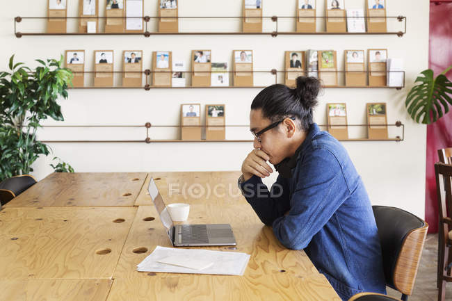 Japanese businessman sitting at a table in a co-working space, using laptop computer. — Stock Photo