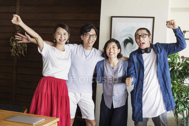 Group of Japanese professionals in a co-working space, smiling and cheering, looking in camera. — Stock Photo