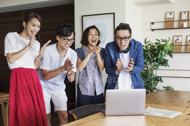 Group of Japanese professionals looking at laptop computer in a co-working space, smiling and cheering. — стокове фото