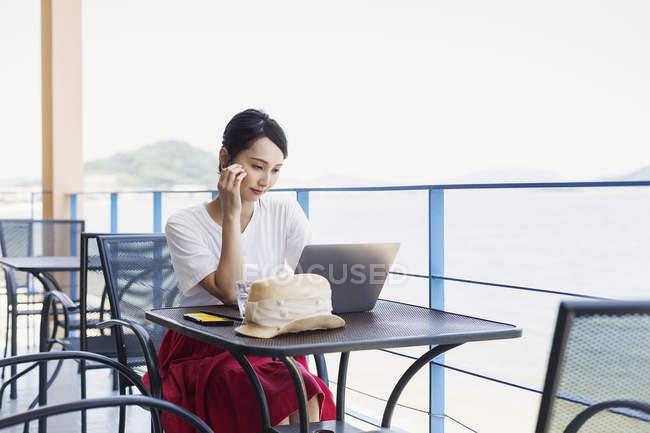 Femme japonaise professionnelle assise sur le balcon d'un espace de co-travail, à l'aide d'un ordinateur portable . — Photo de stock
