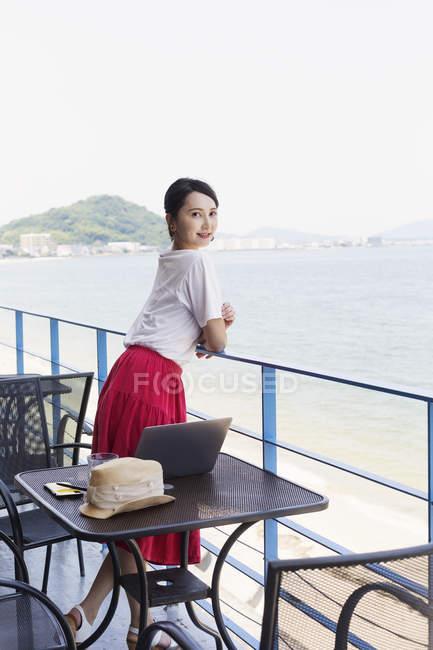 Femme japonaise professionnelle debout sur le balcon d'un espace de co-travail, ordinateur portable sur la table . — Photo de stock