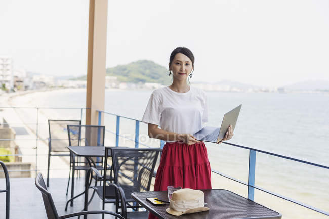 Femme d'affaires japonaise debout sur le balcon d'un espace de co-travail, à l'aide d'un ordinateur portable . — Photo de stock