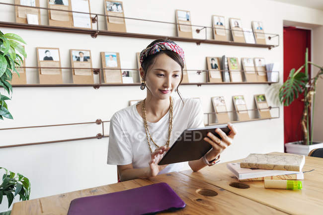 Female Japanese professional sitting at table in a co-working space, using digital tablet and laptop, holding book. — Stock Photo