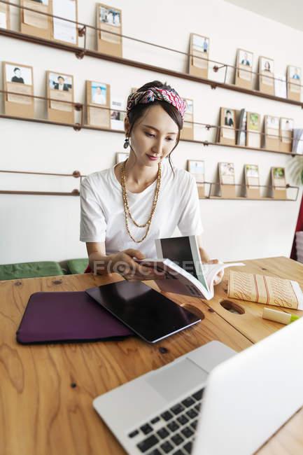 Femme japonaise professionnelle assise à table dans un espace de co-travail, en utilisant une tablette numérique et un ordinateur portable, tenant un livre . — Photo de stock