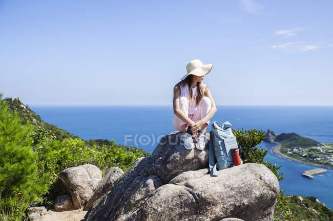 Femme japonaise portant un chapeau assis sur des rochers sur une falaise . — Photo de stock