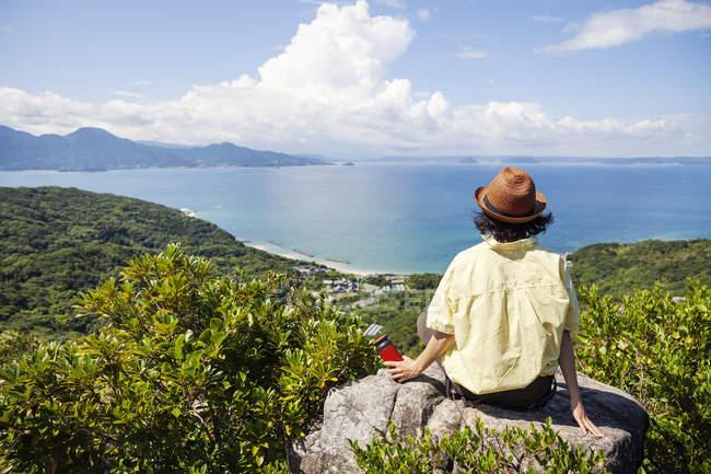 Mulher usando chapéu sentado em rochas em um penhasco, olhando para o oceano . — Fotografia de Stock