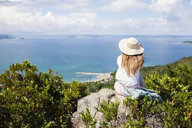 Donna che indossa il cappello seduta su rocce su una scogliera e guardando la vista . — Foto stock