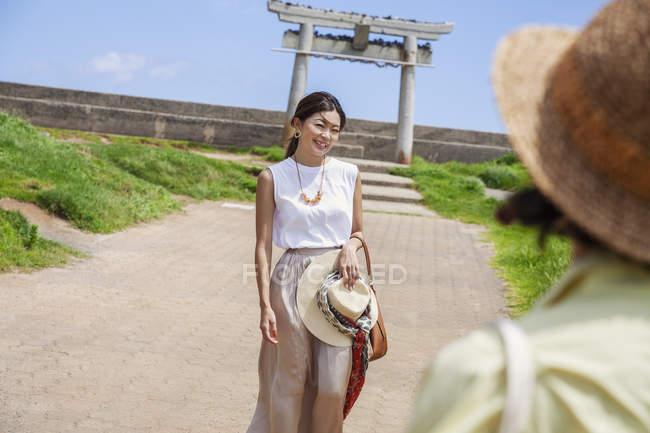 Deux Japonaises portant des chapeaux debout sur un chemin, prenant des photos . — Photo de stock