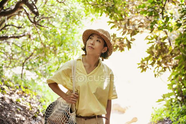 Donna giapponese che indossa cappello escursioni in una foresta . — Foto stock