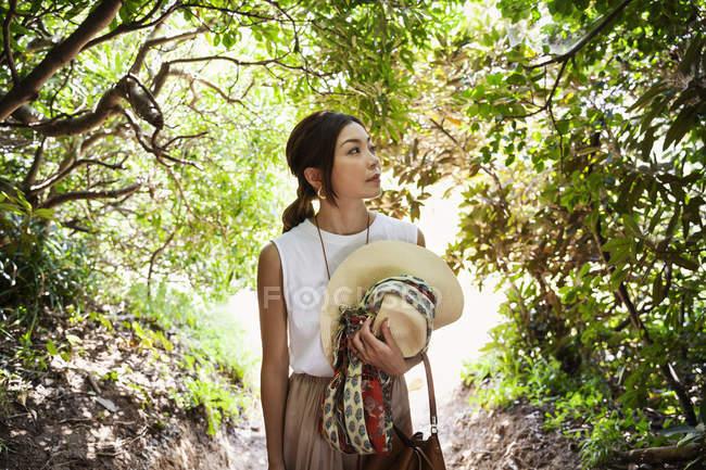 Femme japonaise portant chapeau randonnée dans une forêt . — Photo de stock