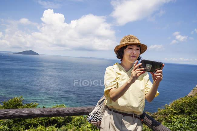 Japanese woman wearing hat standing on a cliff, taking selfie with mobile phone. — Stock Photo