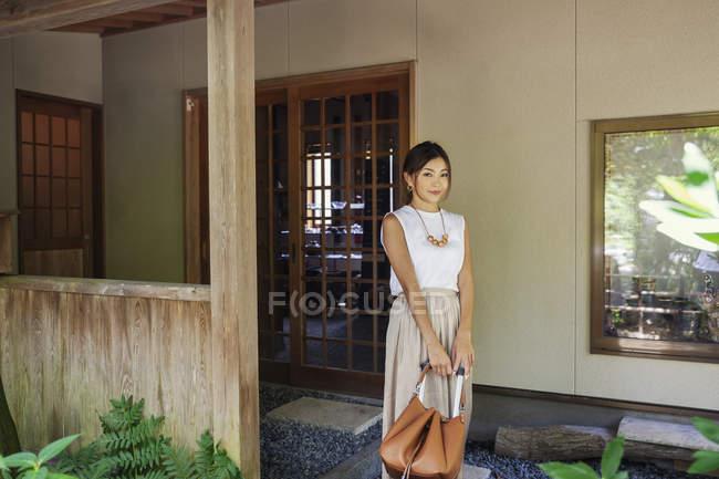 Femme japonaise debout sur un porche, tenant un sac à main . — Photo de stock