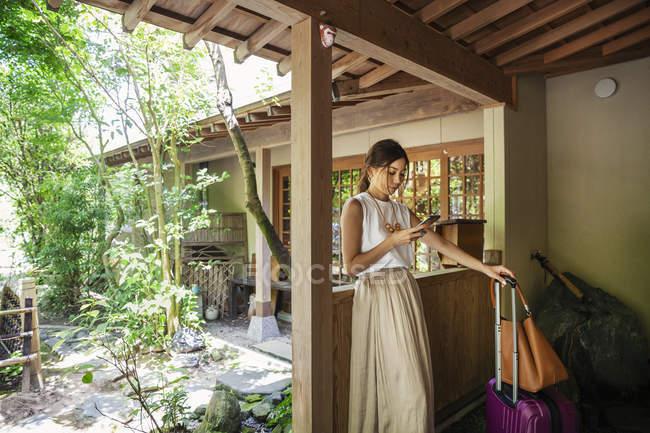 Femme japonaise debout sur un porche, en utilisant un téléphone mobile, tenant valise et sac à main . — Photo de stock
