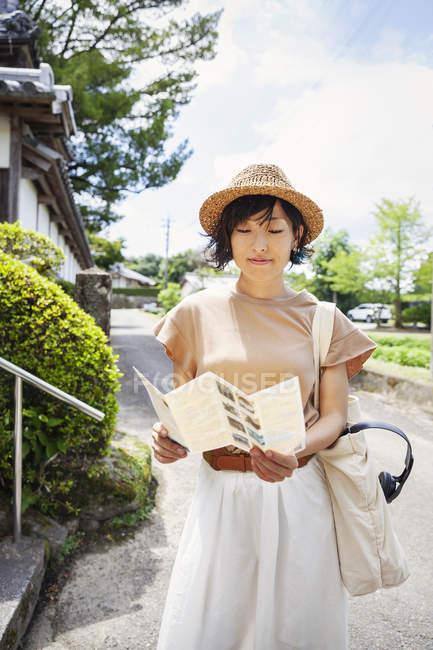 Mujer japonesa usando sombrero y sosteniendo mapa de pie fuera del templo budista . - foto de stock