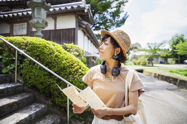 Donna giapponese indossando cappello e tenendo la mappa in piedi fuori tempio buddista . — Foto stock