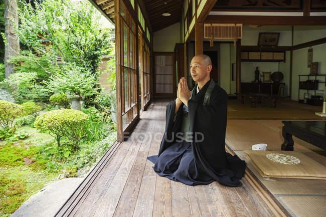 Prêtre bouddhiste agenouillé dans le temple bouddhiste, priant . — Photo de stock